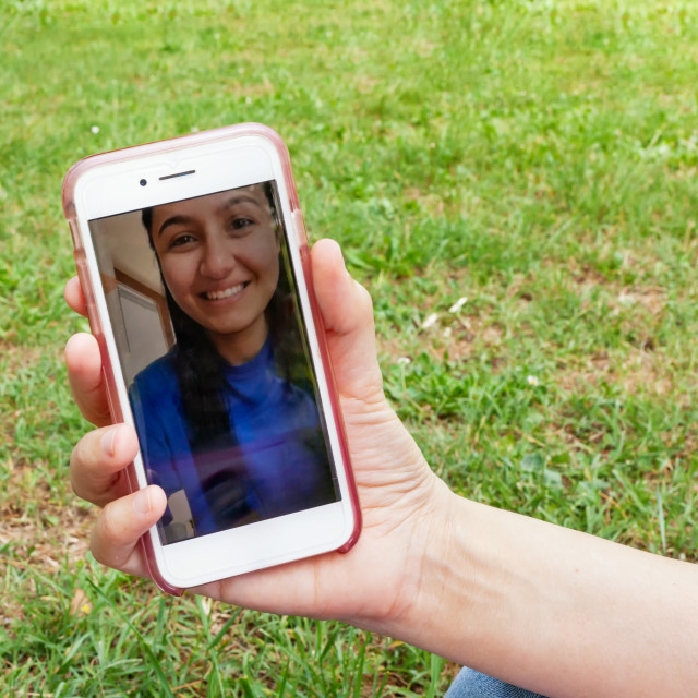 """Close-up of a smartphone in video call with a young smiling girl."" stock image"