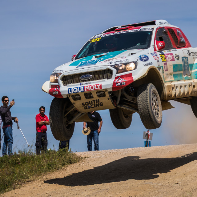 """A Ford Ranger off-road race car jumps high over a road"" stock image"