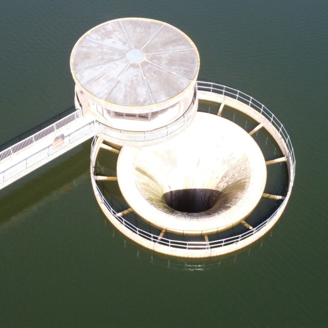 """Aerial shot of a reservoir shaft spillway."" stock image"