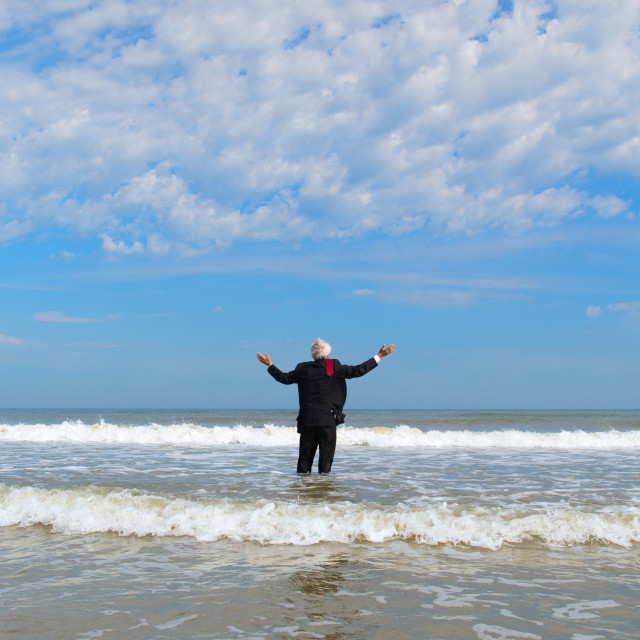 """Business man standing at the beach"" stock image"