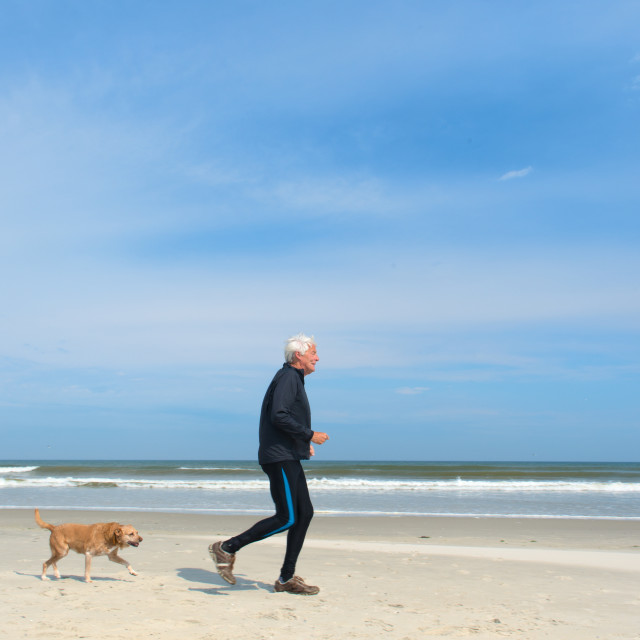 """Senior man running at the beach"" stock image"
