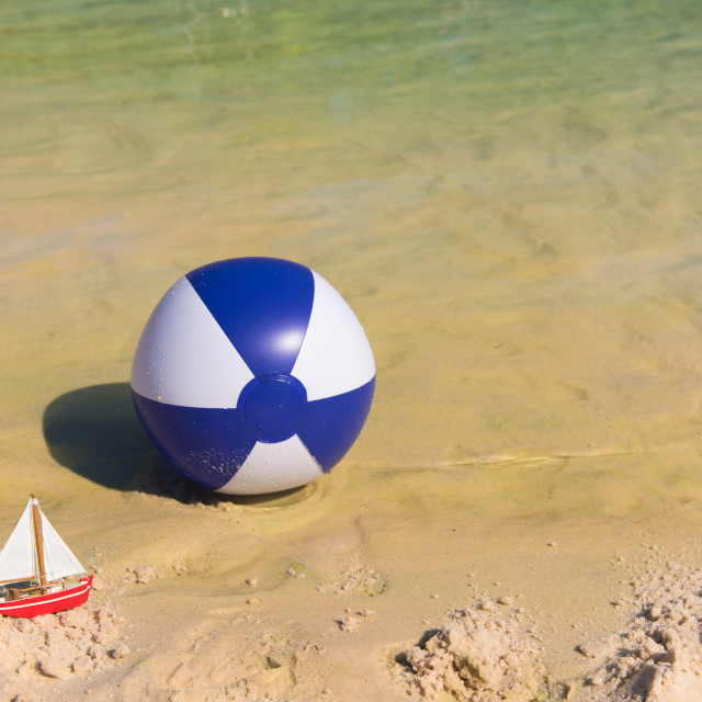 """Toy boat and Inflatble beach ball floating on water"" stock image"