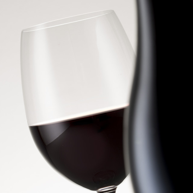 """""""A glass of red wine with a bottle in the foreground"""" stock image"""