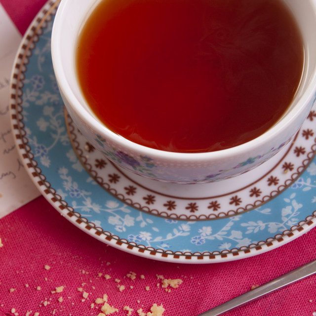 """""""A delicious cup of black tea ona a pink placemat"""" stock image"""