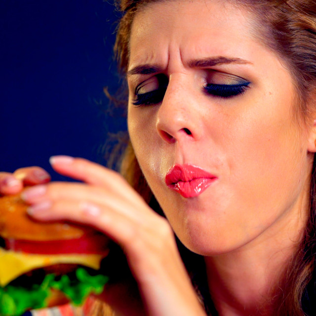 """Girl in food places eats burger"" stock image"