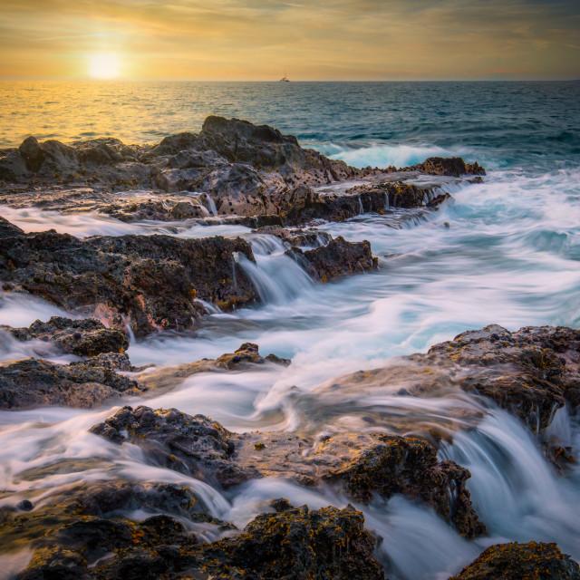 """Rocky coastline at sunset"" stock image"