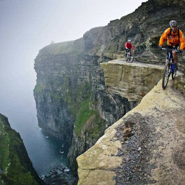 """""""CLARE, IRELAND - OCTOBER 17, 2006. Professional mountain bikers, Hans Rey and Steve Peat, riding on the Cliffs of Moher. 200m above the Atlantic Ocean"""" stock image"""