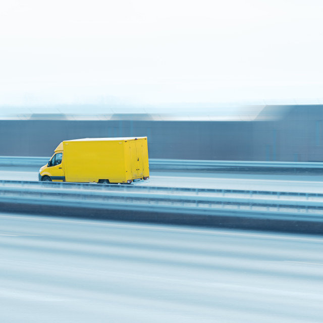 """""""Delivery truck on the highway. Yellow van in motion"""" stock image"""
