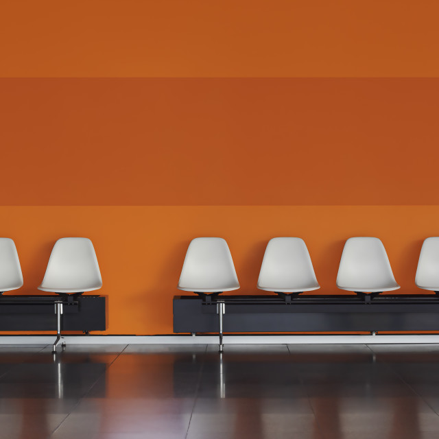 """""""Empty chairs in a row White chairs against the orange wall."""" stock image"""