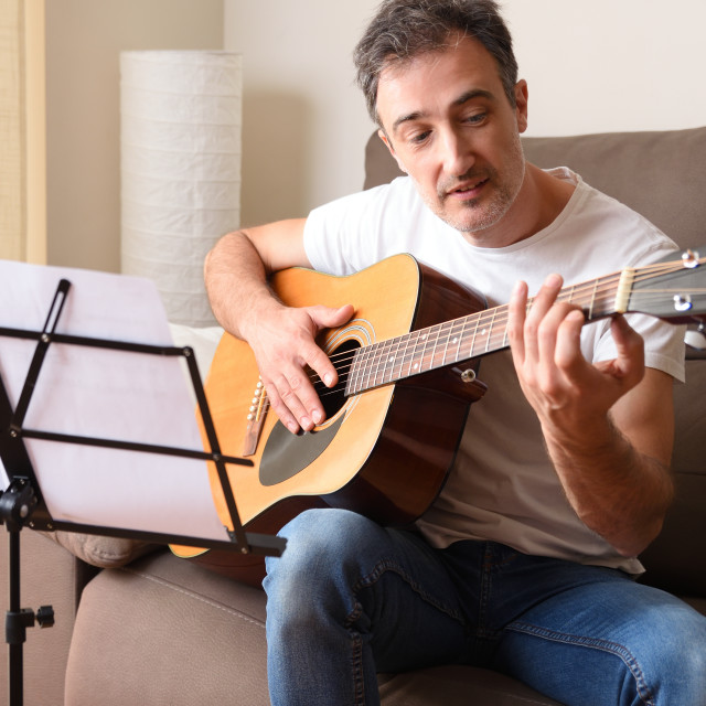 """""""Adult man learning to play guitar at home"""" stock image"""