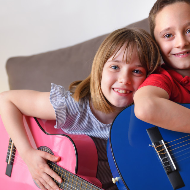 """""""Children smiling and having fun with guitar in hand"""" stock image"""