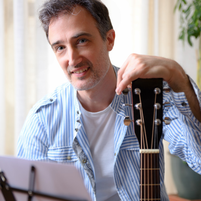 """""""Closeup smiling man leaning on a guitar eyeing at home"""" stock image"""