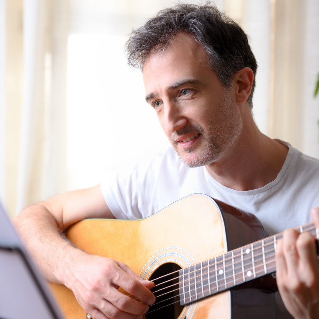 """""""Closeup smiling man playing a song on guitar at home"""" stock image"""
