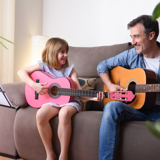 """""""Father daughter playing guitar looking at each other with complicity"""" stock image"""