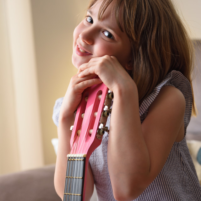 """""""Girl holding the headstock of a guitar looking and smiling"""" stock image"""