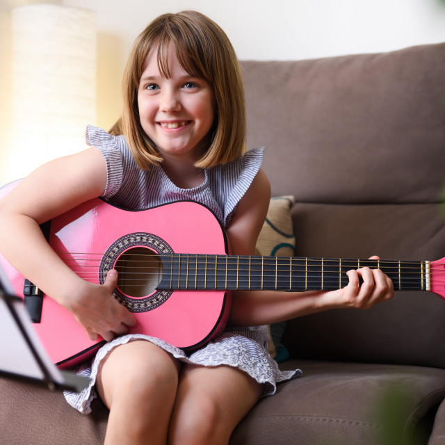 """""""Girl laughing practicing guitar sitting on sofa at home"""" stock image"""