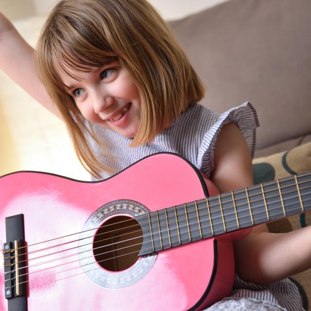 """Girl practicing guitar raising hand success gesture at home"" stock image"