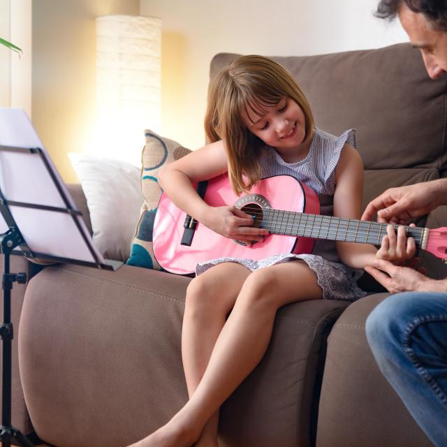 """""""Guitar teacher teaching a girl in her living room"""" stock image"""