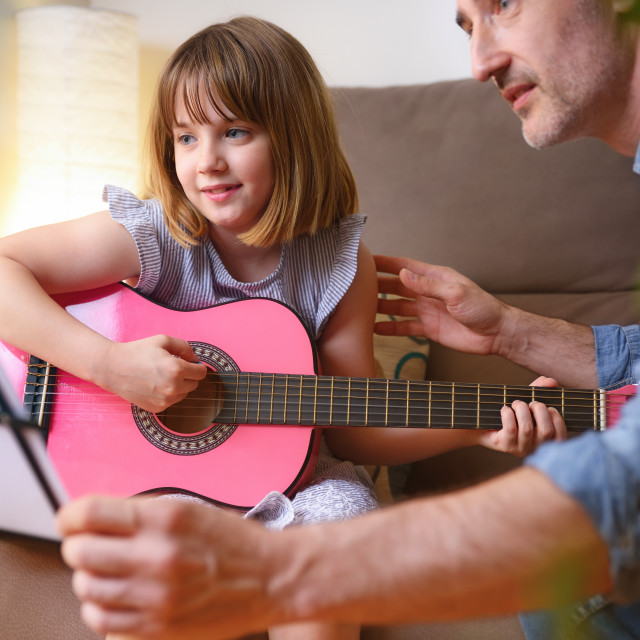 """""""Little girl learning to play the guitar with private teacher"""" stock image"""