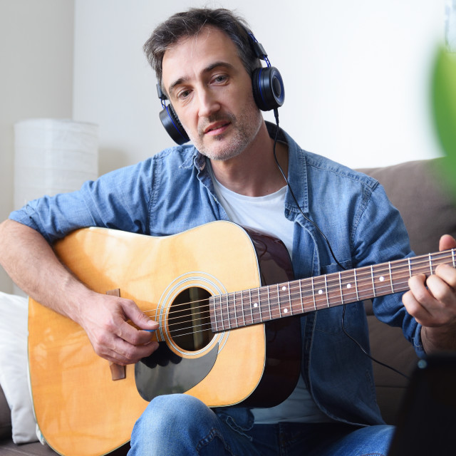 """""""Man learning to play guitar with online teacher at home"""" stock image"""