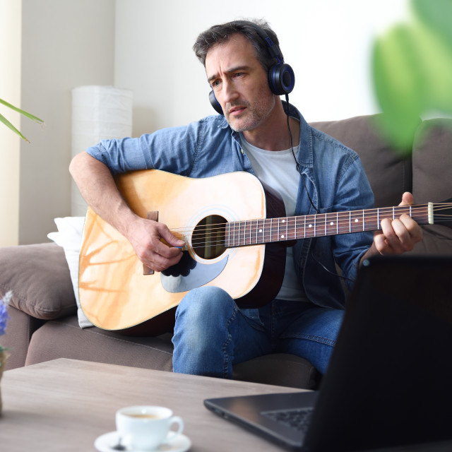 """""""Man listening to music from laptop headphones and playing guitar"""" stock image"""