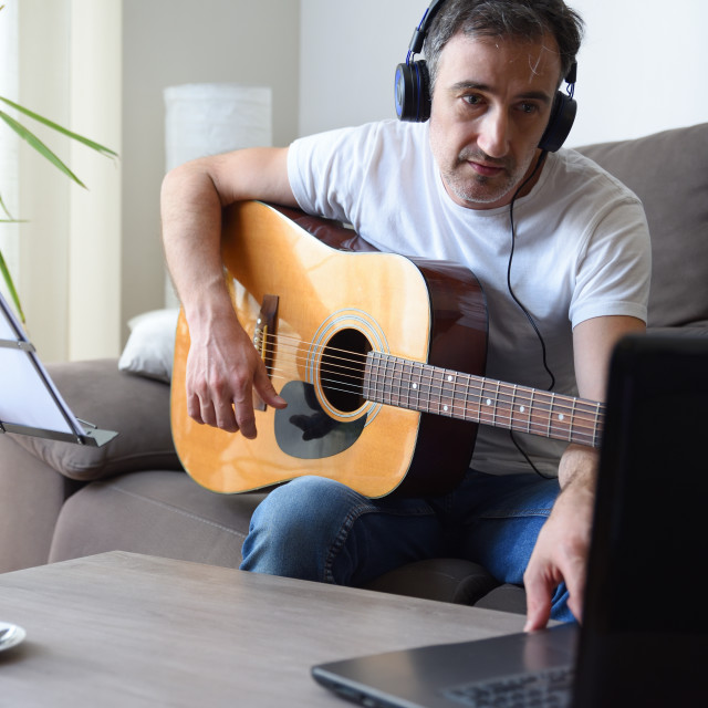 """""""Man listening and playing songs with guitar at home"""" stock image"""