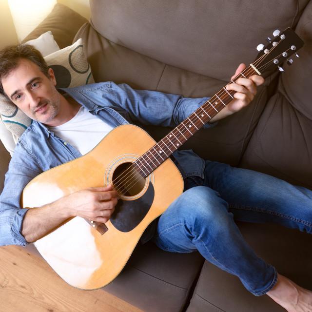 """Man lying on sofa playing guitar at home top detail"" stock image"