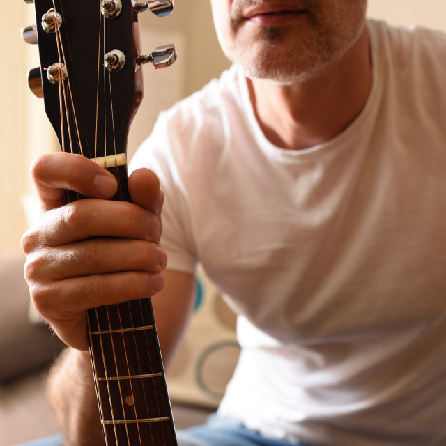 """""""Man picking up acoustic guitar by the neck detail"""" stock image"""