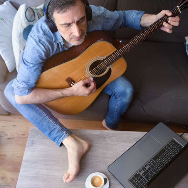 """""""Man playing guitar and listening and looking at laptop top"""" stock image"""