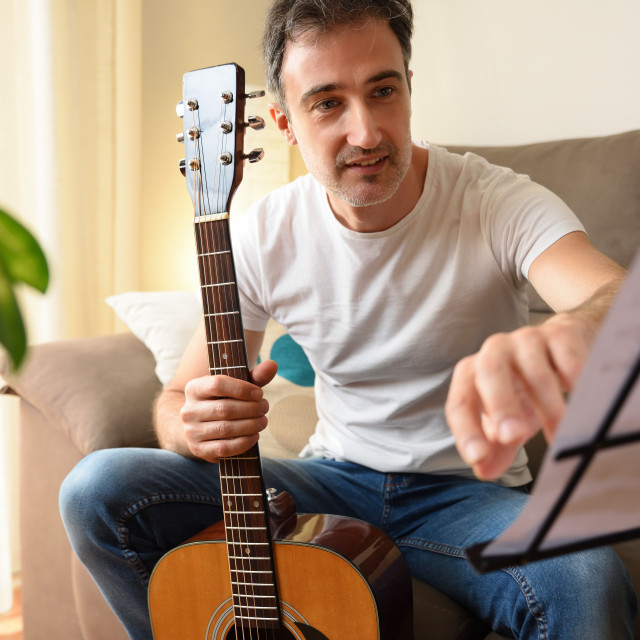 """""""Man practicing songs from a score with his acoustic guitar"""" stock image"""