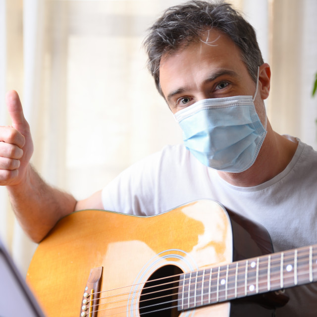 """""""Man with guitar and mask with ok gesture at home"""" stock image"""