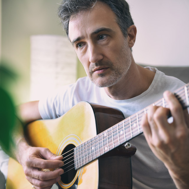 """""""Musician playing acoustic guitar close up in a room"""" stock image"""