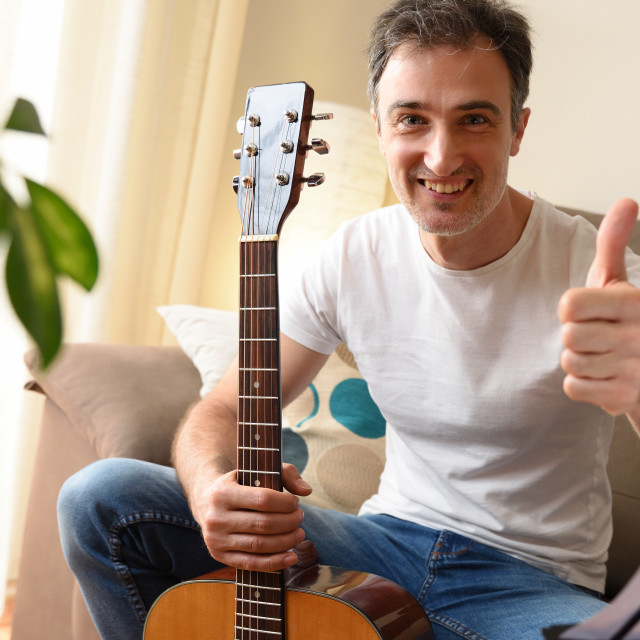 """""""Smiling man with guitar and ok gesture eyeing at home"""" stock image"""