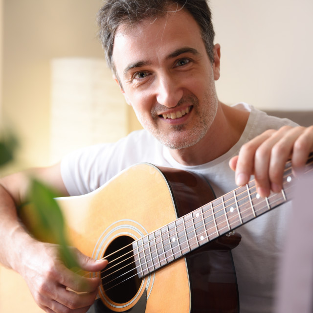 """""""Smiling man with guitar in hands eyeing at home detail"""" stock image"""