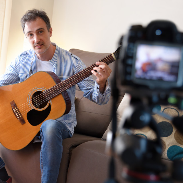 """""""Video Blogger doing review of a guitar recording at home"""" stock image"""