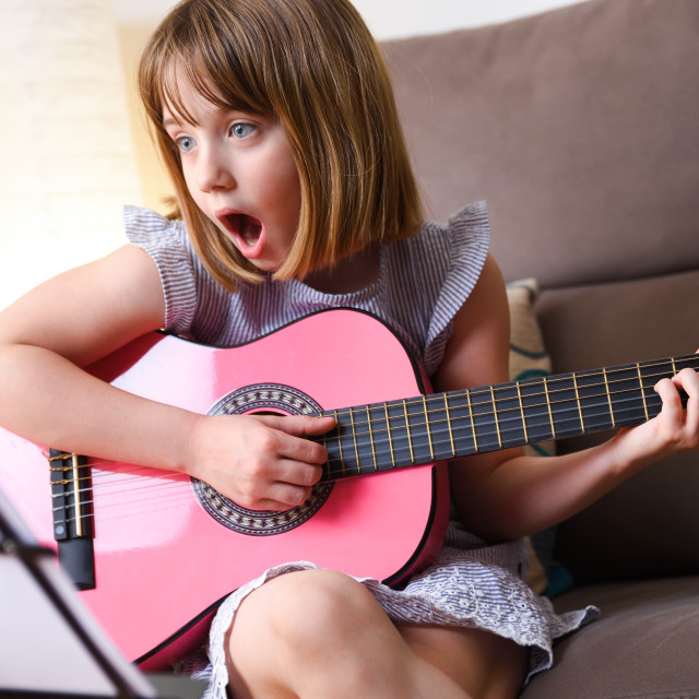 """""""Surprised girl practicing the guitar looking at a sheet music"""" stock image"""