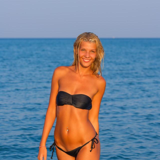 """One woman in a bikini walking through a shallow sea at dusk"" stock image"