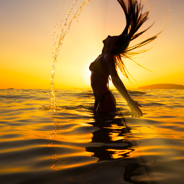 """""""Woman in the sea at sunset flipping her hair"""" stock image"""