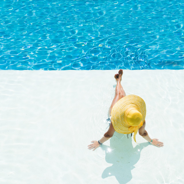 """""""woman in a hat sitting on the edge of the pool"""" stock image"""