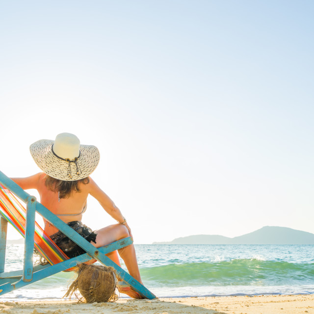"""""""Young woman in hat sitting on beach"""" stock image"""