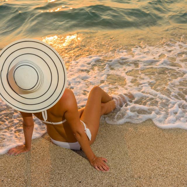 """Woman in bikini and straw hat on the beach"" stock image"