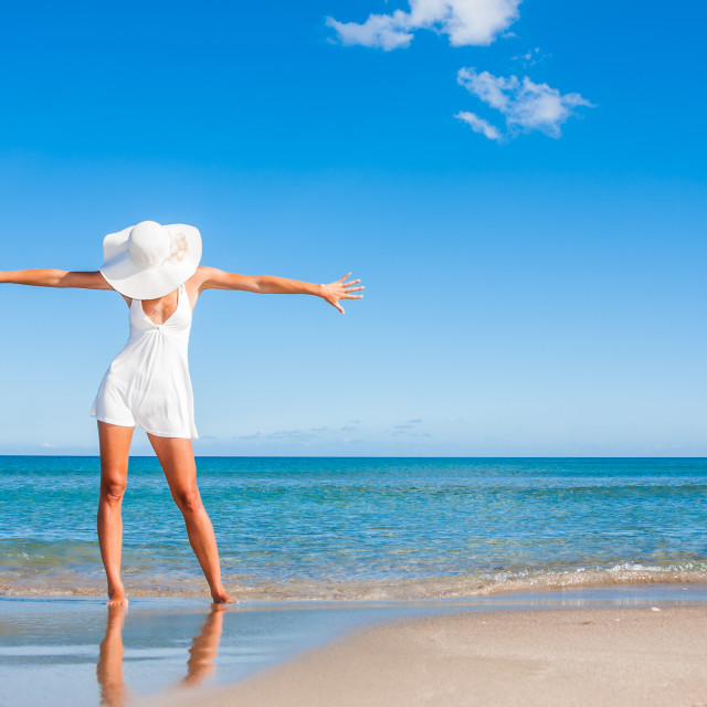 """""""Young woman standing on a beach and enjoying the sun"""" stock image"""