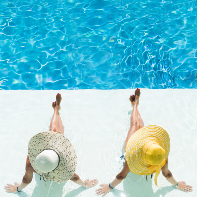 """""""Two women in a hat sitting on the edge of the pool"""" stock image"""