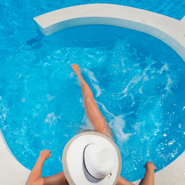 """""""Woman relaxing in infinity swimming pool"""" stock image"""
