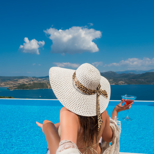 """""""Woman relaxing at the infinity swimming pool"""" stock image"""
