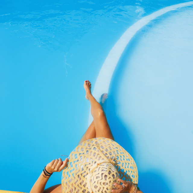 """""""Pretty woman in a hat enjoying a swimming pool"""" stock image"""
