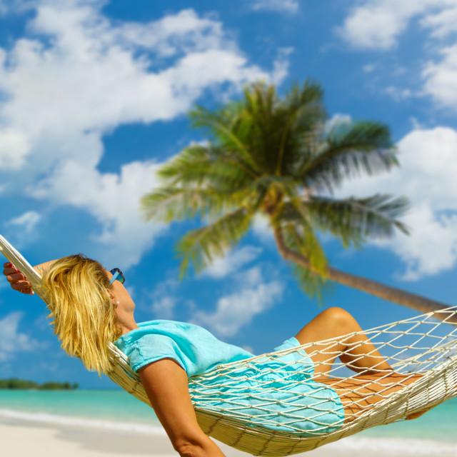"""Woman sitting in hammock on the beach."" stock image"