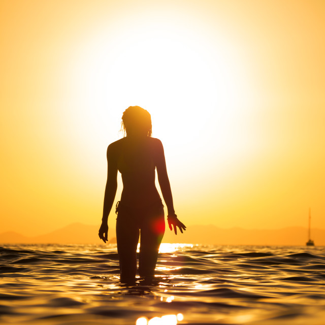 """""""young woman walking in the sea at sunset"""" stock image"""