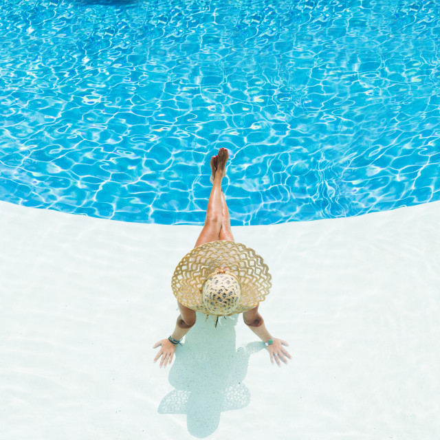 """""""beautiful woman in a hat sitting on the edge of the pool"""" stock image"""