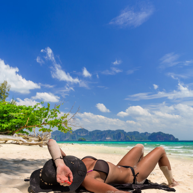 """""""Woman with straw hat laying on the beach in Koh Poda island Thai"""" stock image"""